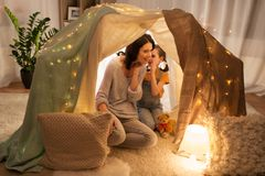 Happy family whispering in kids tent at home Stock Photos