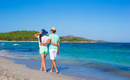 Happy family at white beach during tropical. Back view of young couple walking at beach during tropical vacation in Sardinia Stock Photos