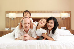 Happy family on white bed Royalty Free Stock Images