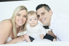 Happy family on white bed in the bedroom Royalty Free Stock Images