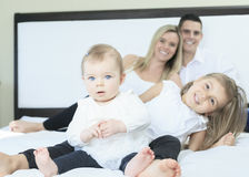 Happy family on white bed in the bedroom Stock Photos