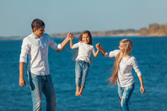 Happy family who playing on the beach. Concept of Stock Photography
