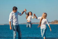 Happy family who playing on the beach. Concept of. Friendly family stock photo