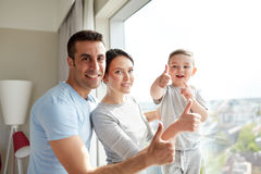 Happy family at window. People and family concept - happy mother, father and little son showing thumbs up at home window Royalty Free Stock Photography