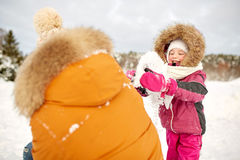 Happy family in winter clothes playing with snow Stock Photography