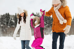 Happy family in winter clothes walking outdoors Stock Photo
