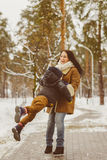 Happy family in winter clothing. laughing Mother and son playing fun game outdoor Royalty Free Stock Images