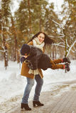 Happy family in winter clothing. laughing Mother and son playing fun game outdoor Royalty Free Stock Photos
