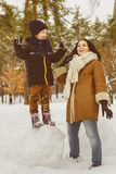 Happy family in winter clothing. laughing Mother and son playing fun game outdoor Stock Images