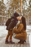 Happy family in winter clothing. Little son kissing his happy smiling mother Stock Images