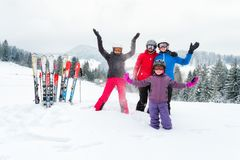 Happy family in winter clothing at ski resort - skiing, winter, snow, fun - mom and daughters enjoying winter vacations. Happy family in winter clothing at the stock image