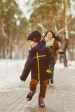 Happy family in winter clothing. Smiling son runs away from his mother outdoor Royalty Free Stock Images