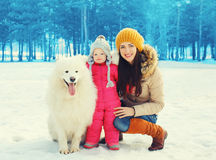 Happy family in winter day, smiling mother and child walking with white Samoyed dog Stock Photo