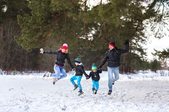 Happy family in the winter forest. Royalty Free Stock Photo