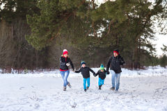 Happy family in the winter forest. Royalty Free Stock Photos