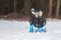 Happy family in the winter forest. Stock Photos