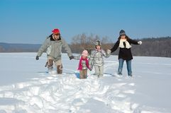 Happy family in winter, having fun and playing with snow outdoors on holiday weekend Stock Images