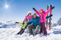 Happy family in winter holiday. Laughing family in winter vacation with ski sport on snowy mountains. Happy men and women with sons having fun and looking at Stock Images