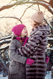 Happy Family in Winter Park. Mother and Daughter looking at each other Royalty Free Stock Image