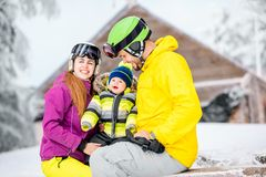 Happy family during the winter vacations. Happy family with baby boy in winter spots clothes sitting on the bench outdoors during the winter vacations royalty free stock images