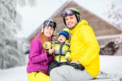 Happy family during the winter vacations. Happy family with baby boy in winter spots clothes sitting on the bench outdoors during the winter vacations royalty free stock photos