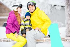 Happy family during the winter vacations. Happy family with baby boy in winter spots clothes sitting on the bench outdoors during the winter vacations royalty free stock image
