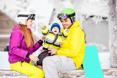Happy family during the winter vacations. Happy family with baby boy in winter spots clothes sitting on the bench outdoors during the winter vacations stock image