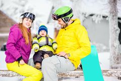 Happy family during the winter vacations. Happy family with baby boy in winter spots clothes sitting on the bench outdoors during the winter vacations stock photos