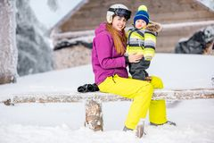 Happy family during the winter vacations. Happy mother with baby boy in winter spots clothes sitting on the bench outdoors during the winter vacations royalty free stock image