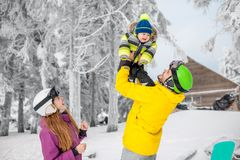 Happy family during the winter vacations. Happy family playing with baby boy standing in winter spots clothes outdoors during the winter vacations royalty free stock images