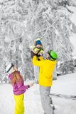 Happy family during the winter vacations. Happy family playing with baby boy standing in winter spots clothes outdoors during the winter vacations stock photography