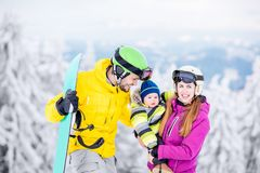 Happy family during the winter vacations. Portrait of a happy family with baby boy in winter sports clothes standing with snowboard during the winter vacations royalty free stock photo