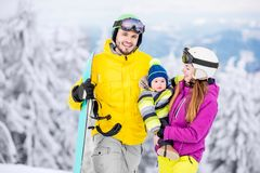 Happy family during the winter vacations. Portrait of a happy family with baby boy in winter sports clothes standing with snowboard during the winter vacations royalty free stock image