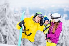 Happy family during the winter vacations. Portrait of a happy family with baby boy in winter sports clothes standing with snowboard during the winter vacations stock images
