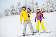 Happy family during the winter vacations. Portrait of a happy family with baby boy riding on the snowboards during the winter vacations on the snowy mountains royalty free stock photography