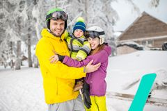 Happy family during the winter vacations. Portrait of a happy family with baby boy standing in winter spots clothes outdoors during the winter vacations royalty free stock photography