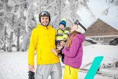 Happy family during the winter vacations. Portrait of a happy family with baby boy standing in winter spots clothes outdoors during the winter vacations royalty free stock image