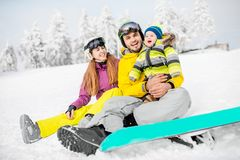 Happy family during the winter vacations. Portrait of a happy family with baby boy during the winter vacations on the beautiful snow-covered mountains royalty free stock photos