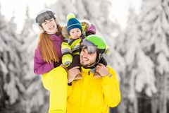 Happy family during the winter vacations. Portrait of a happy family playing with baby boy during the winter vacations on the beautiful mountains with snow royalty free stock photography