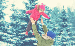 Happy family on winter walk. Dad throws up baby girl Royalty Free Stock Images