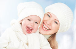 Happy family on a winter walk. Mother and baby daughter in the white hats. Laughing Royalty Free Stock Photos