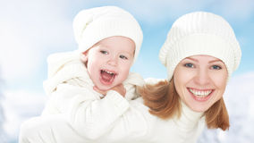 Happy family on a winter walk. Mother and baby daughter in the white hats Stock Images