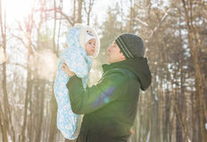 Happy family on a winter walk in nature. Dad throws up baby boy Stock Photos
