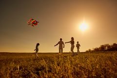 Free Happy Family With A Kite Playing At Sunset In The Field Royalty Free Stock Image - 116783506