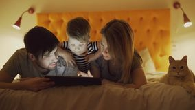 Free Happy Family With Little Son And Funny Cat Lying In Bed At Home And Using Tablet Computer For Playing Game Before Stock Image - 106079141