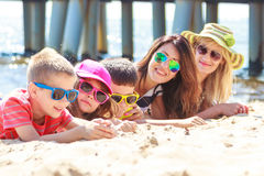 Happy family women kids sunbathing on beach. Stock Photo