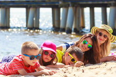 Happy family women kids sunbathing on beach. Stock Photo