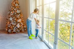 Mother and daughter near large window and Christmas tree at home royalty free stock photography