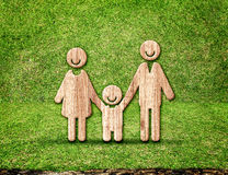 Happy family wood icon in green grass room,Eco concept.  royalty free stock photo