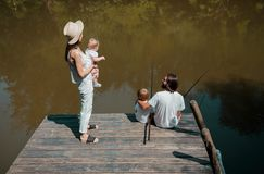 Happy family on the wooden pier. Mother is holding in the arms l royalty free stock images